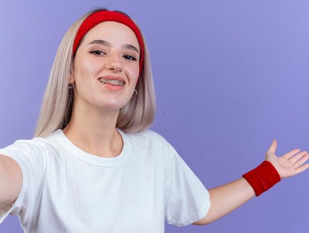 Uśmiechnięta młoda kobieta sportowy z szelkami na sobie opaskę i opaski na rękę trzyma otwartą rękę i patrzy na przód na białym tle na fioletowej ścianie