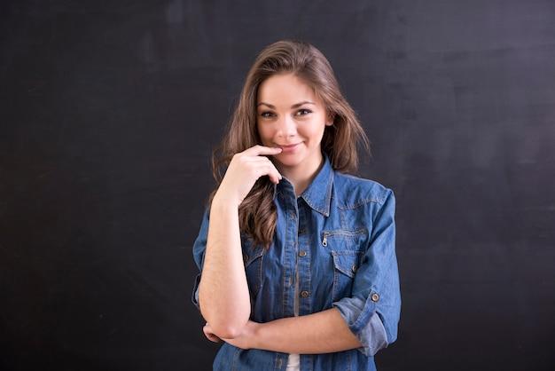 Uśmiechnięta młoda kobieta stoi na blackboard.