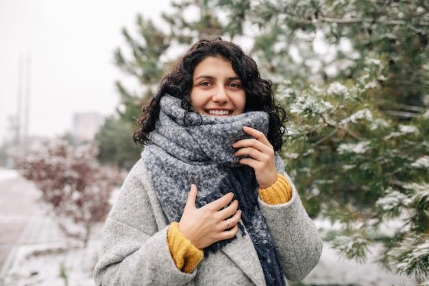Uśmiechnięta młoda kobieta stoi w mroźnym śnieżnym zimowym parku.