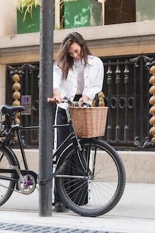 Uśmiechnięta młoda kobieta stoi w pobliżu roweru na chodniku