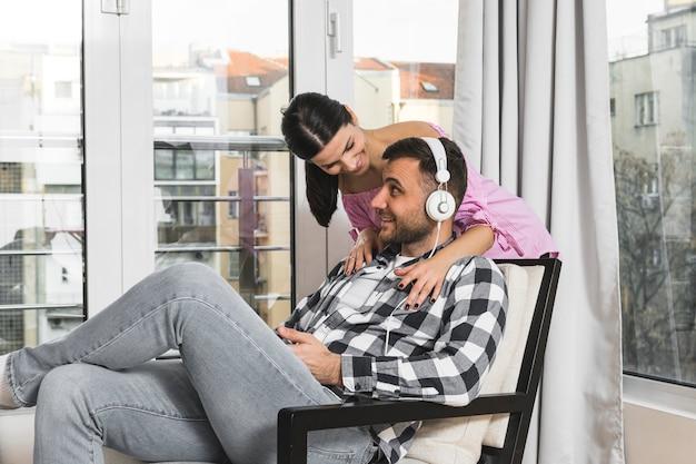 Uśmiechnięta młoda kobieta stoi za mężczyzną siedzi na krześle słuchania muzyki na słuchawkach