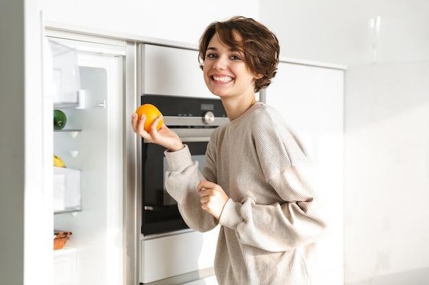 Uśmiechnięta młoda kobieta stojąca przy lodówce, trzymając pomarańczowy