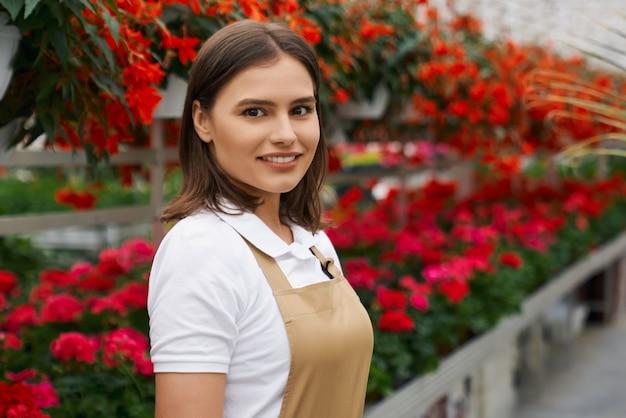 Uśmiechnięta młoda kobieta stojąca w dużej nowoczesnej szklarni
