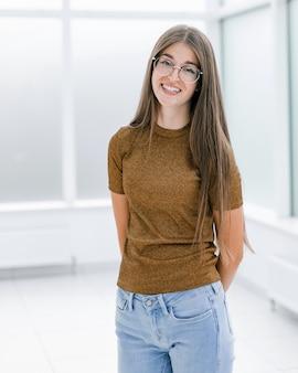 Uśmiechnięta młoda kobieta stojąca w jasnym biurze