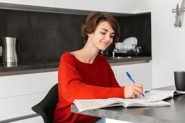 Uśmiechnięta młoda kobieta studiuje przy stole w kuchni w domu