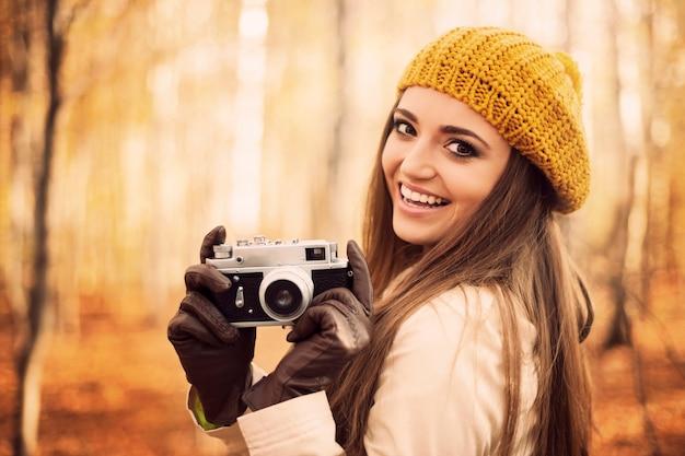Uśmiechnięta młoda kobieta trzyma aparat retro