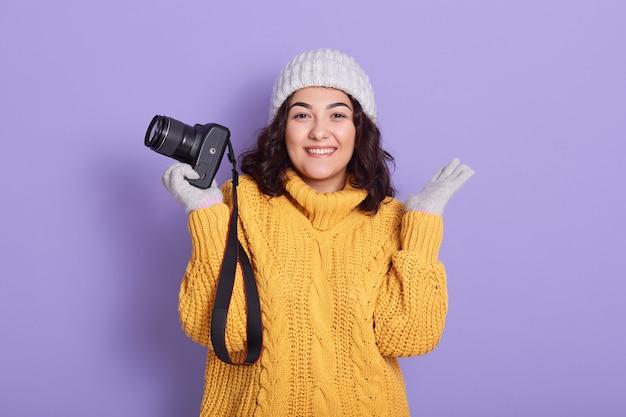 Uśmiechnięta młoda kobieta trzyma aparat w jednej ręce i rozkładając drugą dłoń na bok