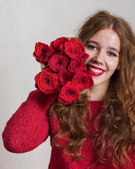 Uśmiechnięta młoda kobieta trzyma bukiet róż