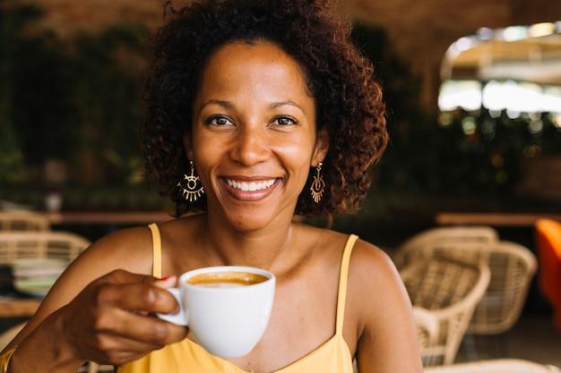 Uśmiechnięta młoda kobieta trzyma filiżankę kawy w ręce