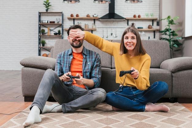 Uśmiechnięta młoda kobieta trzyma joystick zakrywający jej męża oczy podczas gdy bawić się wideo grę