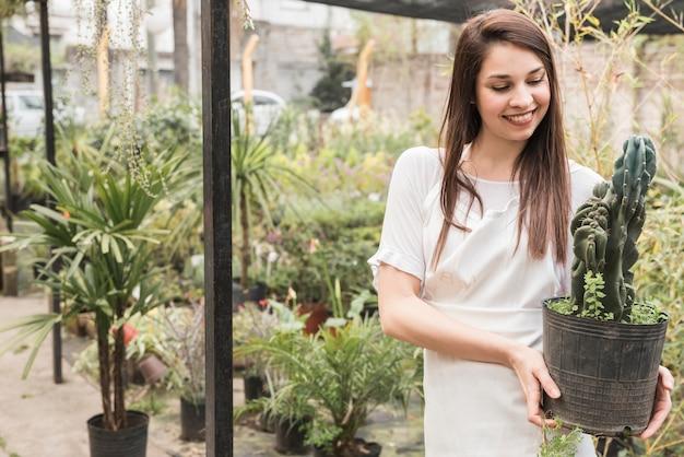Uśmiechnięta młoda kobieta trzyma kaktusowej doniczkowej rośliny w szklarni