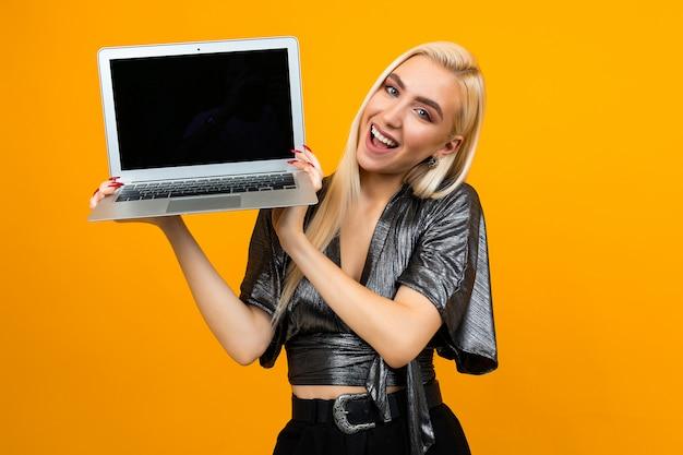 Uśmiechnięta młoda kobieta trzyma laptop z pustym ekranem na żółtej ścianie
