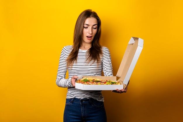 Uśmiechnięta młoda kobieta trzyma pakiet z gorącą świeżą pizzą na żółto.