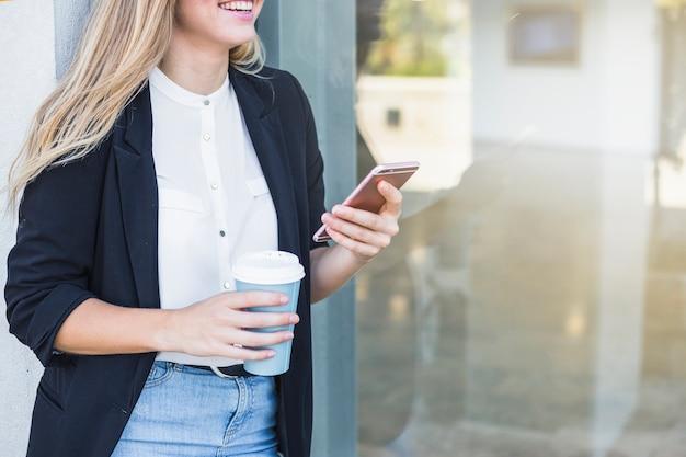 Uśmiechnięta młoda kobieta trzyma papierową filiżankę i telefon komórkowego