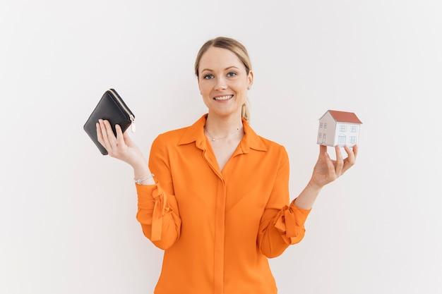 Uśmiechnięta młoda kobieta trzyma portfel i miniaturowy model domu na białym ścianie