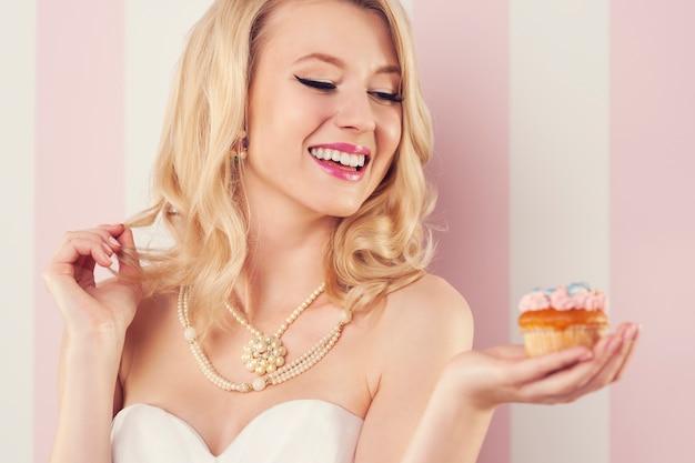 Uśmiechnięta młoda kobieta trzyma różową bułeczkę