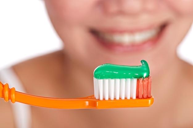 Uśmiechnięta młoda kobieta trzyma szczoteczkę do zębów z zdrowymi zębami