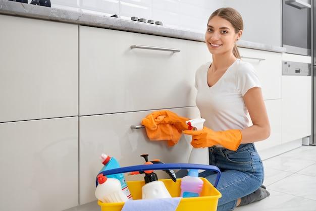 Uśmiechnięta młoda kobieta trzyma szmatkę i detergent w kuchni