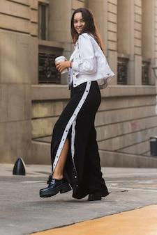 Uśmiechnięta młoda kobieta trzyma takeaway filiżanki stać plenerowy