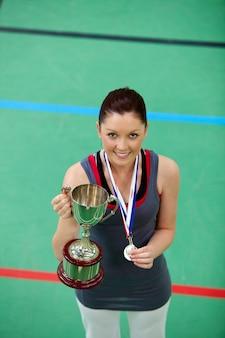 Uśmiechnięta młoda kobieta trzyma trophee i medal
