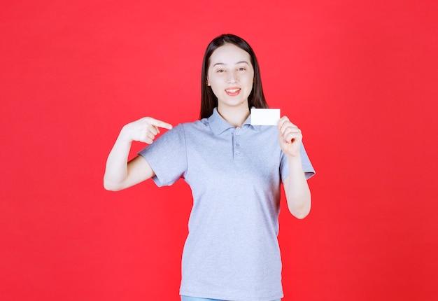 Uśmiechnięta młoda kobieta trzyma wizytówkę i sama wskazuje palcem
