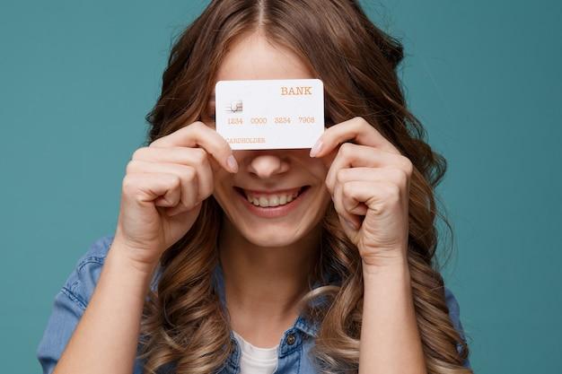 Uśmiechnięta młoda kobieta trzyma złotą kartę kredytową