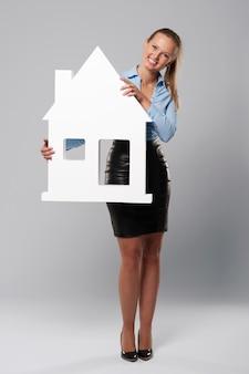 Uśmiechnięta młoda kobieta trzyma znak domu