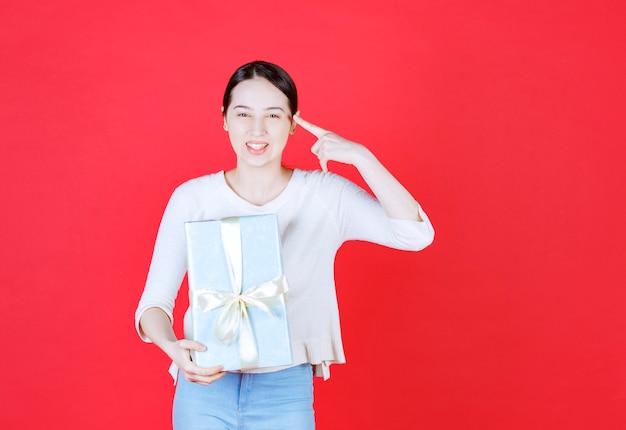 Uśmiechnięta młoda kobieta trzymająca pudełko i wskazująca palcem na głowę