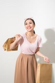 Uśmiechnięta młoda kobieta trzymająca torby na zakupy i uśmiechnięta