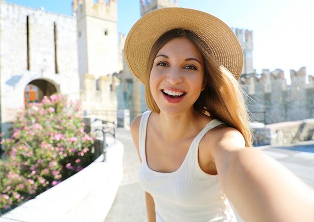 Uśmiechnięta młoda kobieta turystycznych ma autoportret w sirmione we włoszech. piękna dziewczyna robi selfie z zamkiem sirmione w tle, jezioro garda, włochy.