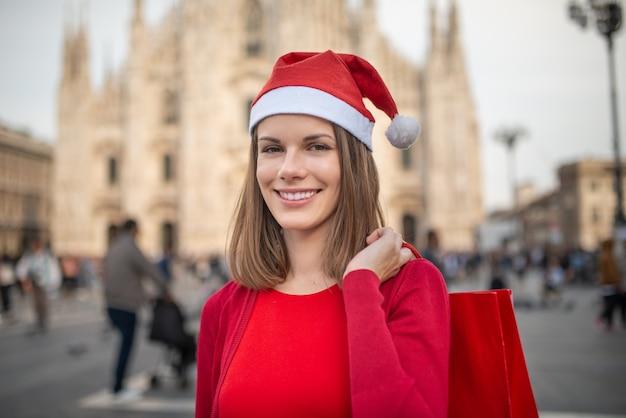 Uśmiechnięta młoda kobieta ubrana na czerwono robi świąteczne zakupy w mediolanie we włoszech