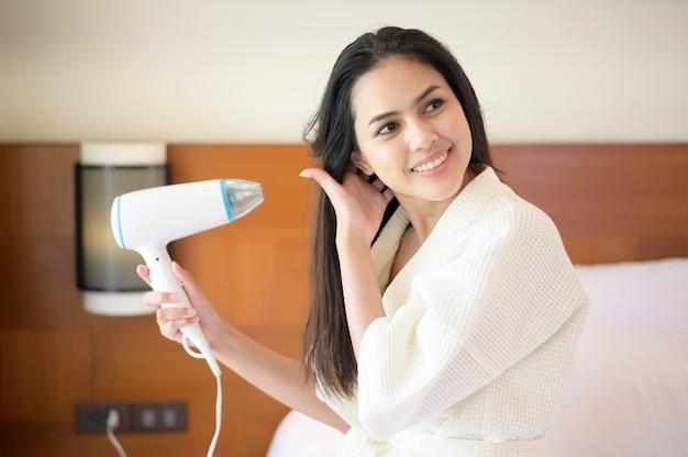 Uśmiechnięta młoda kobieta ubrana w biały szlafrok, susząca włosy suszarką do włosów po prysznic w sypialni