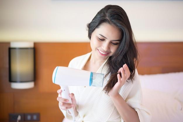 Uśmiechnięta młoda kobieta ubrana w biały szlafrok, suszy włosy suszarką do włosów po prysznic w sypialni