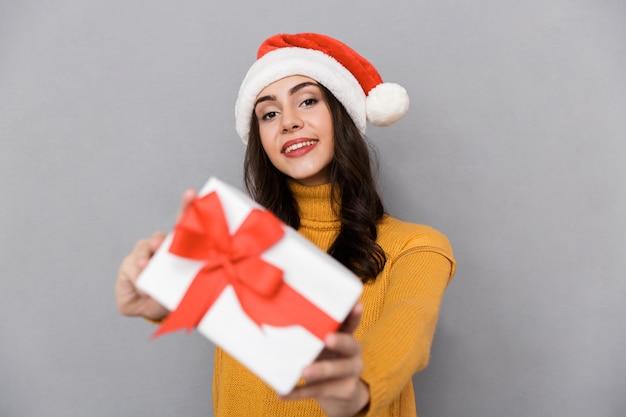 Uśmiechnięta młoda kobieta ubrana w boże narodzenie kapelusz stojący na białym tle na szarym tle, dając obecne pudełko