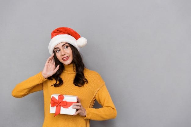 Uśmiechnięta młoda kobieta ubrana w boże narodzenie kapelusz stojący na białym tle na szarym tle, trzymając obecne pudełko, odwracając