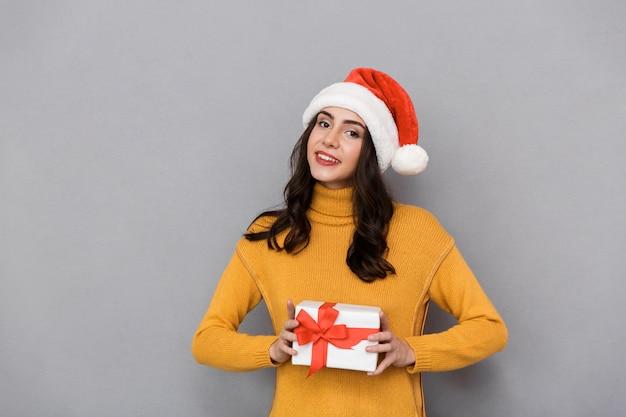 Uśmiechnięta młoda kobieta ubrana w boże narodzenie kapelusz stojący na białym tle na szarym tle, trzymając obecne pudełko