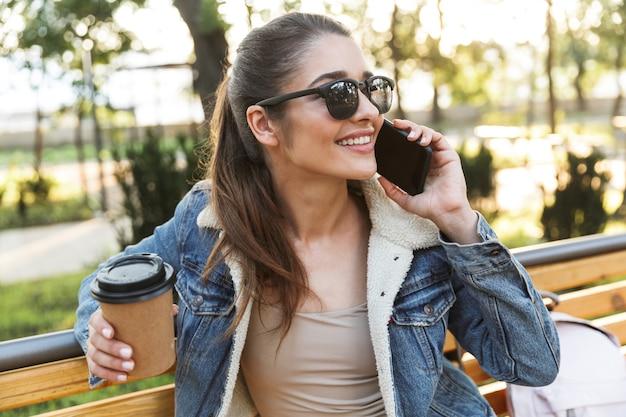 Uśmiechnięta młoda kobieta ubrana w kurtkę i okulary przeciwsłoneczne siedzi na ławce w parku, przy użyciu telefonu komórkowego, pije kawę na wynos
