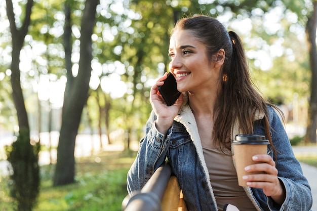 Uśmiechnięta młoda kobieta ubrana w kurtkę i okulary przeciwsłoneczne siedzi na ławce w parku, trzymając filiżankę kawy na wynos
