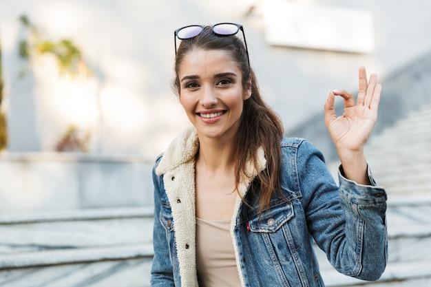 Uśmiechnięta młoda kobieta ubrana w kurtkę siedzi na ławce na zewnątrz, pokazując ok