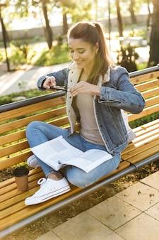 Uśmiechnięta młoda kobieta ubrana w kurtkę siedzi na ławce w parku, czytając magazyn, robienie zdjęć