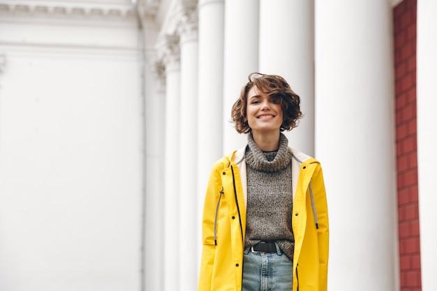 Uśmiechnięta młoda kobieta ubrana w płaszcz