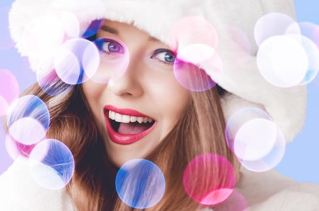 Uśmiechnięta młoda kobieta ubrana w puszyste białe futro