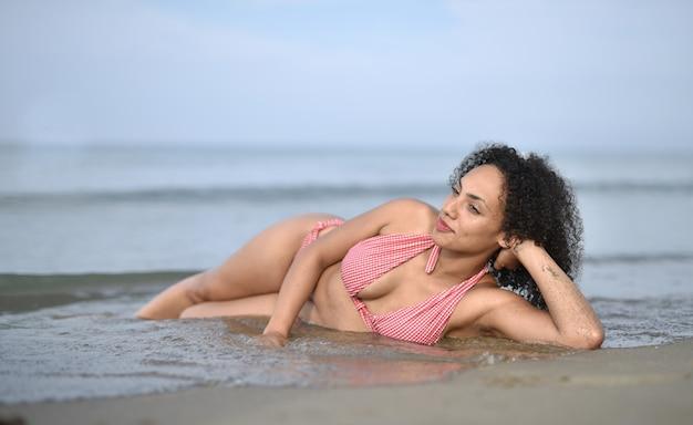 Uśmiechnięta młoda kobieta ubrana w strój kąpielowy na plaży