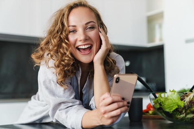 Uśmiechnięta młoda kobieta ubrana w zwykłe ubrania, korzystająca z telefonu komórkowego, opierając się na kuchennym stole