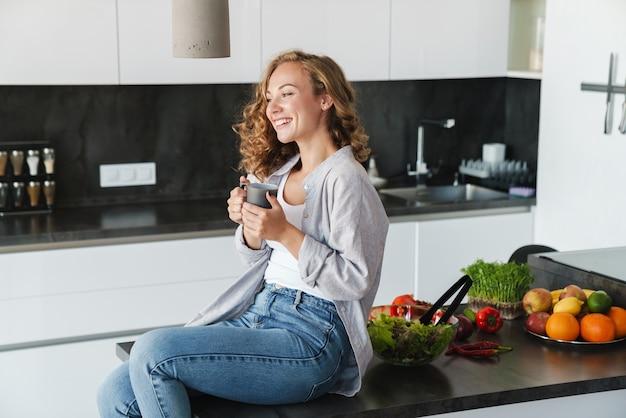Uśmiechnięta młoda kobieta ubrana w zwykłe ubrania po filiżance kawy siedząc na stole w kuchni