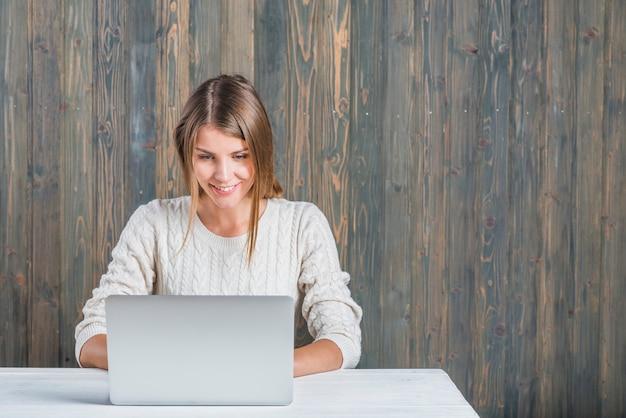 Uśmiechnięta młoda kobieta używa laptop przeciw drewnianej ścianie