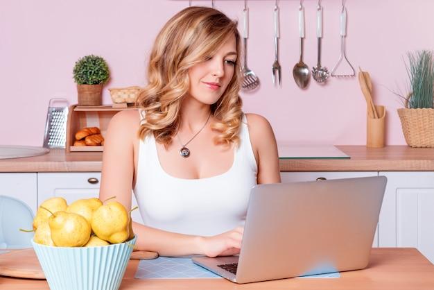 Uśmiechnięta młoda kobieta używa laptop w kuchni w domu. blond kobieta pracuje na komputerze, freelancer lub bloger pracujący w domu