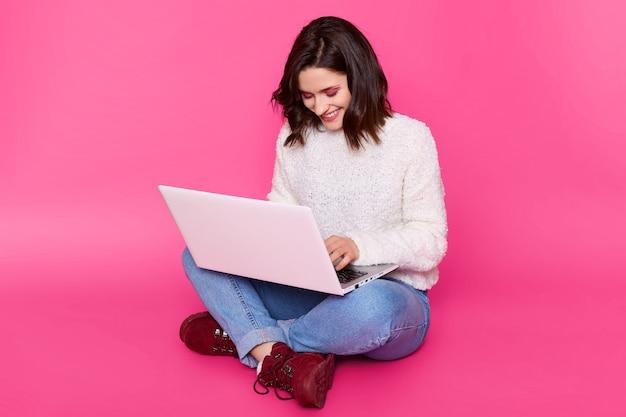 Uśmiechnięta młoda kobieta używa laptopa do zarabiania pieniędzy w internecie. urocza brunetka pracuje online, siedzi ze skrzyżowanymi nogami na podłodze. pani nosi swobodny biały sweter, dżinsy i wygodne bordowe buty.