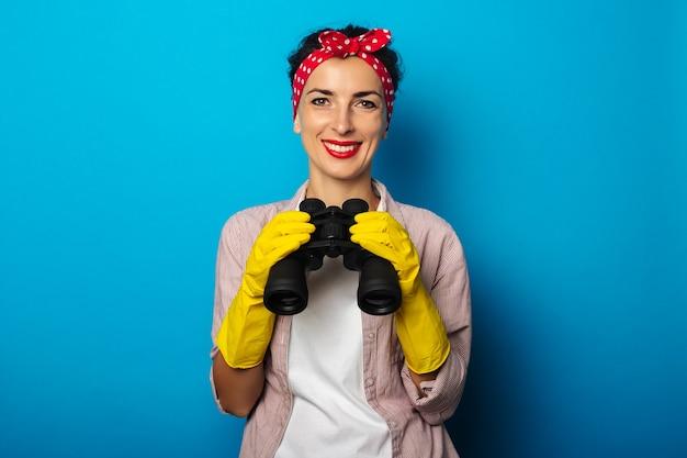 Uśmiechnięta młoda kobieta w bandażach, w rękawiczkach do czyszczenia, trzymając lornetkę na niebieskiej powierzchni