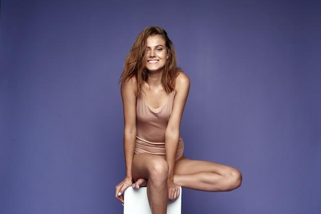Uśmiechnięta młoda kobieta w beżowym body siedzi na sześcianie na fioletowym tle. koncepcja lato. skopiuj miejsce.